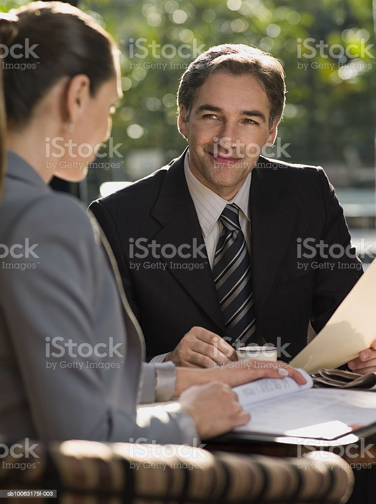 Businessman and woman sitting by table drinking coffee and having discussion foto stock royalty-free