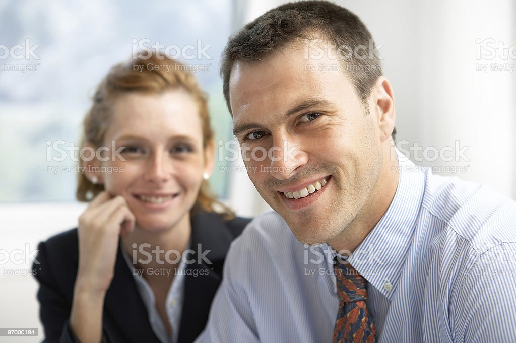 Businessman and woman smiling and looking at camera royalty-free stock photo