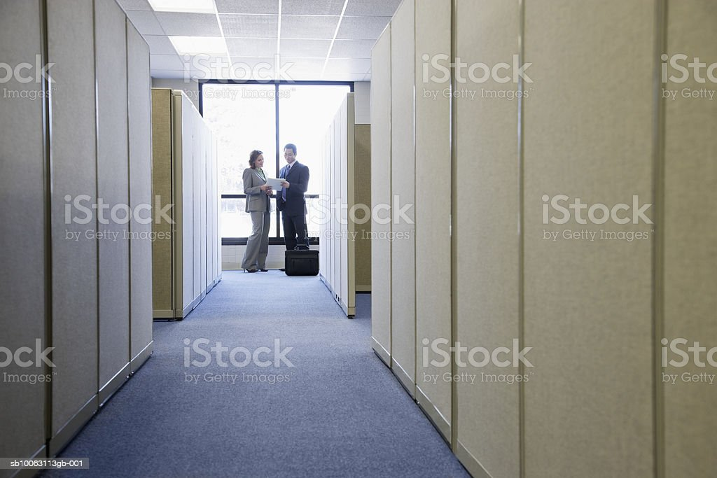 Businessman and woman standing by window in office royalty-free stock photo