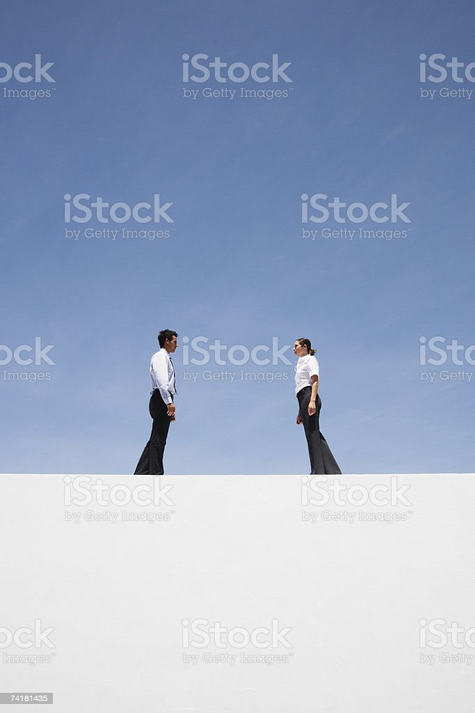 Businessman and woman standing outdoors on wall royalty-free stock photo