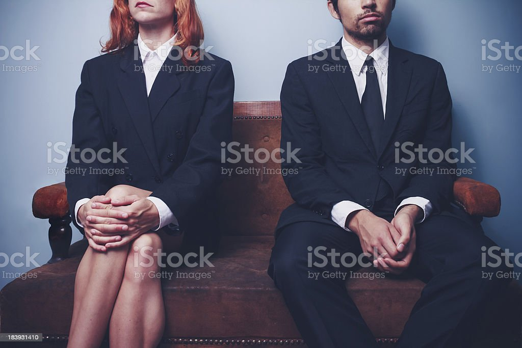 Businessman and woman waiting on sofa in lobby stock photo