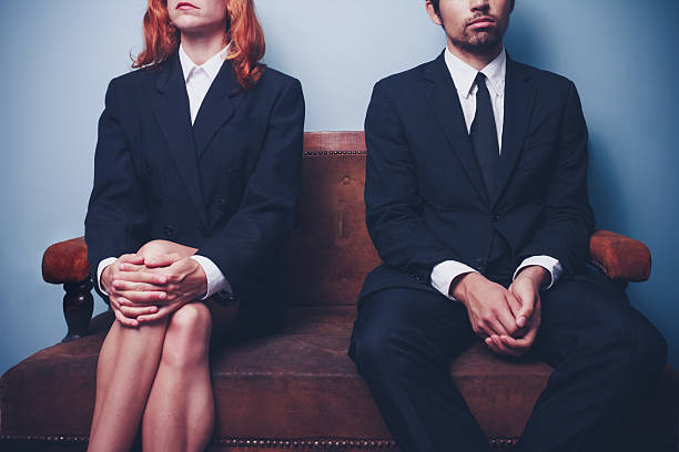 businessman and woman waiting on sofa in lobby - gender stereotypes stock pictures, royalty-free photos & images