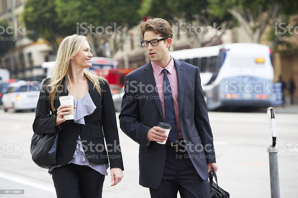 Businessman and woman walking in street with takeaway coffee royalty-free stock photo