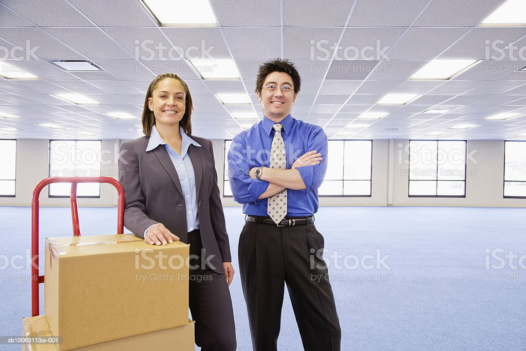 Businessman and woman with boxes on dolly in empty office, smiling, portrait foto stock royalty-free