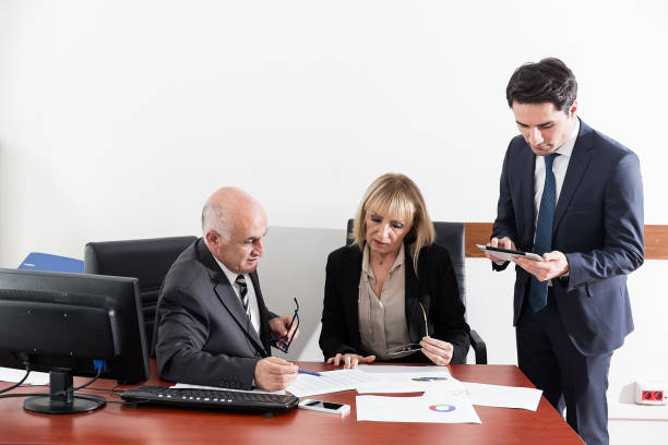 Businessman and woman working at desk Businessman and woman working at desk civil servant stock pictures, royalty-free photos & images