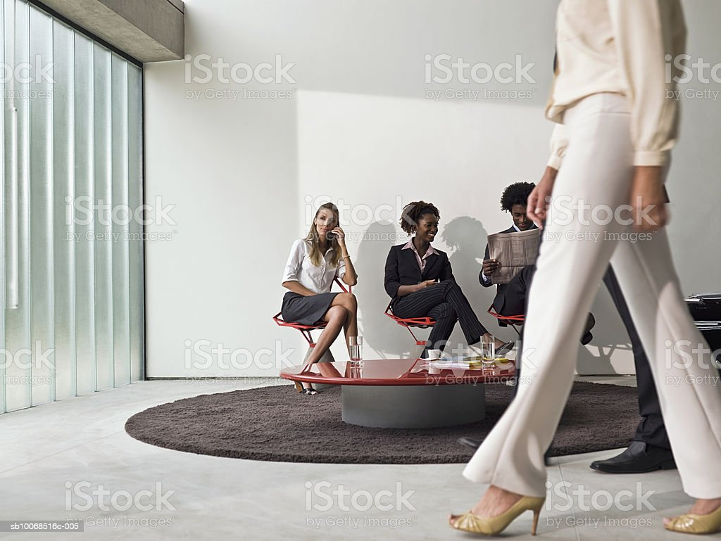Businessman and women sitting in office lobby royalty free stockfoto