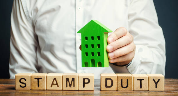 Businessman and wooden blocks with the word Stamp duty and house. Taxes assessed during the transfer of real estate between two parties. Buying housing and land. Property. Stamp Duty Land Tax/ SDLT Businessman and wooden blocks with the word Stamp duty and house. Taxes assessed during the transfer of real estate between two parties. Buying housing and land. Property. Stamp Duty Land Tax/ SDLT between stock pictures, royalty-free photos & images