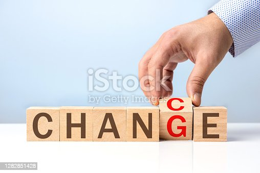 Businessman and wooden letters on a blue background with change concept.