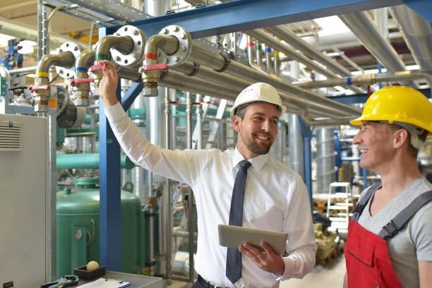 businessman and worker meeting in a factory - maintenance and repair of the industrial plant stock photo