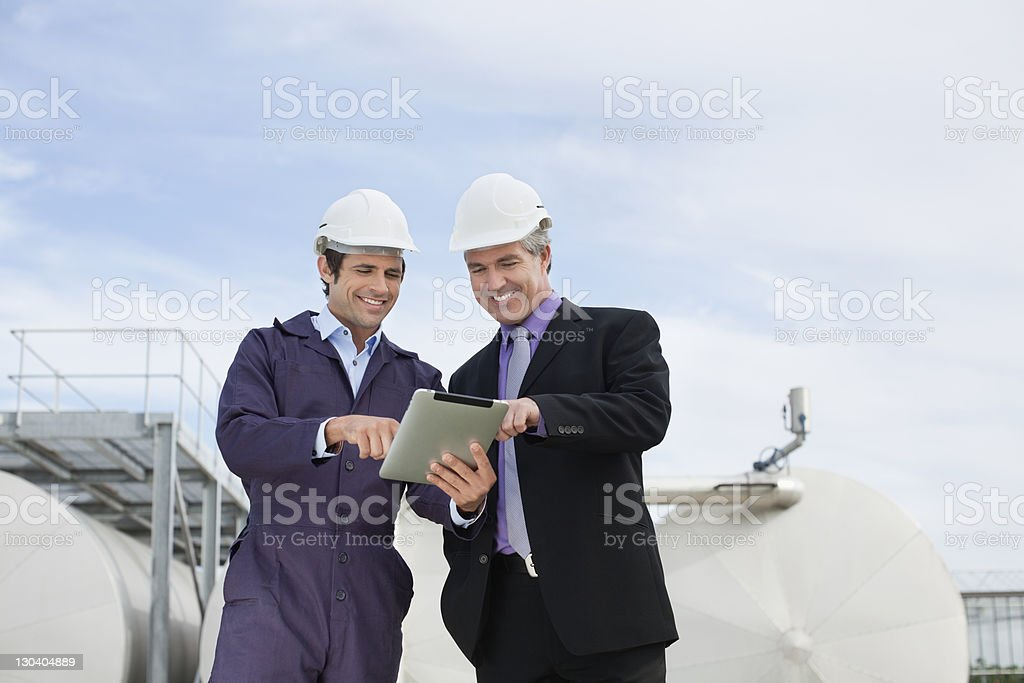 Businessman and worker using tablet computer outdoors royalty-free stock photo
