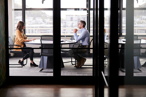 A businessman and young woman meeting for a job interview, full length, seen through glass wall