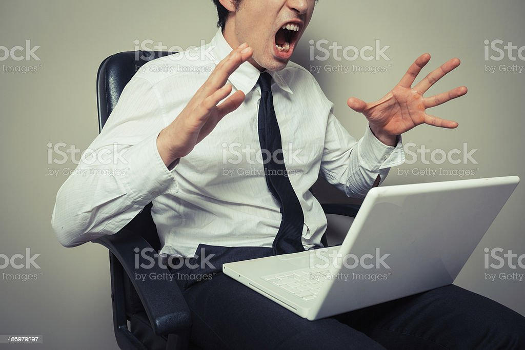 Businessman angry at laptop stock photo
