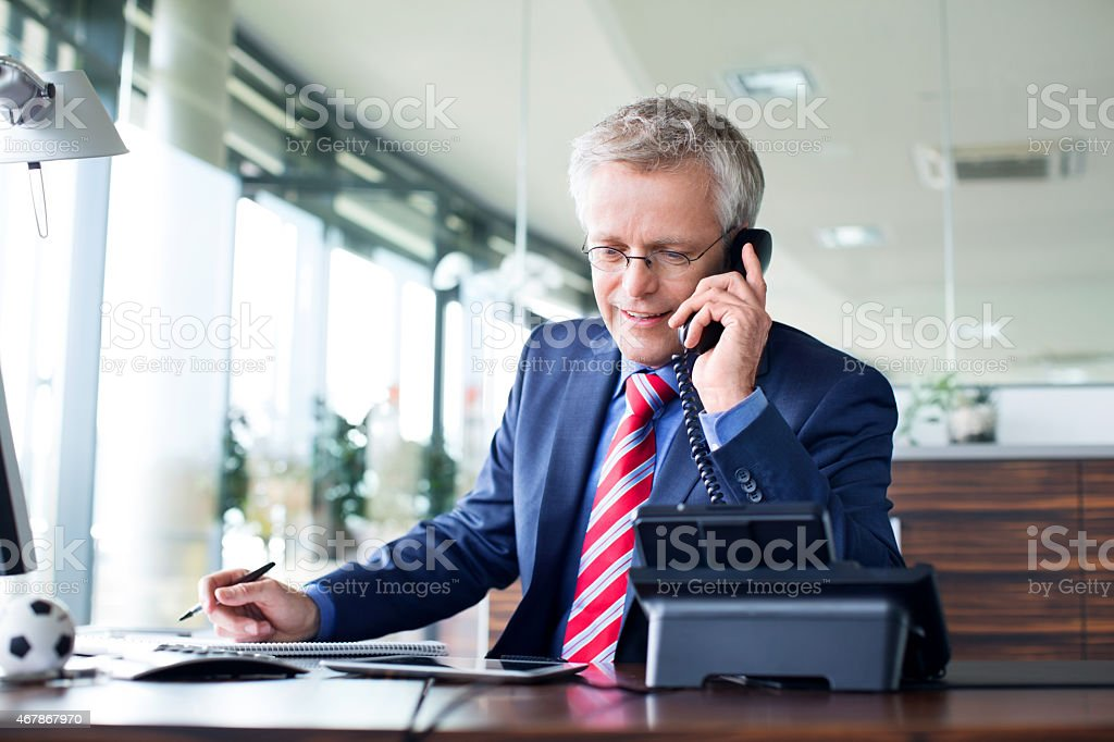 Businessman answering a phone call stock photo