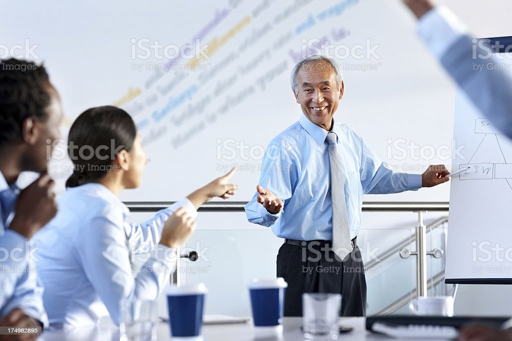 Businessman answering questions in presentation stock photo