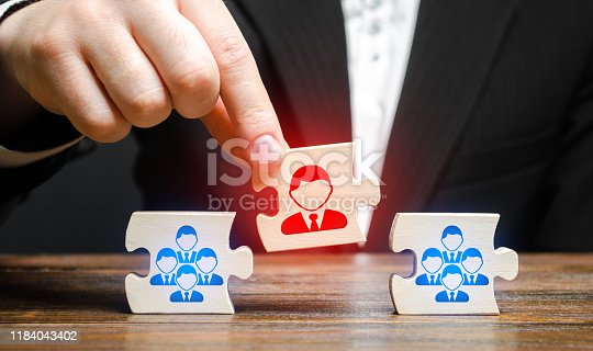istock A businessman appoints a leader to the head of the team. Creation of an effective teams of specialists for the implementation of a new project. HR recruiting. Management appointment. nepotism 1184043402
