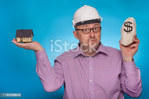 istock A businessman, architect in a piked shirt and hard hat has a house and a bag of dollars in his hand,  on the blue background. 1130058643