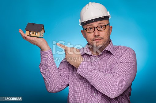 istock A businessman, architect in a piked shirt and hard hat  pointing with the index finger on a house,  on the blue background. 1130058638