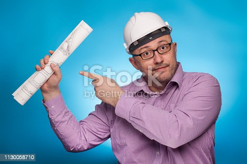 istock A businessman, architect in a piked shirt pointing with the index finger on a blueprint,  on the blue background. 1130058710