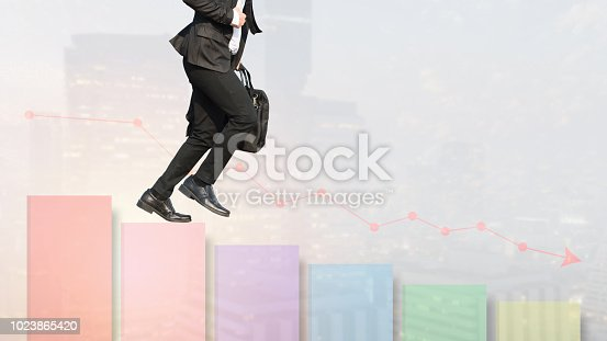 istock Businessman are walking or run down stairs made in the shape of a graph. Chart in the fall. City in the background. Concept Business falling down. Negative trend. Crisis impact. economy going down. 1023865420
