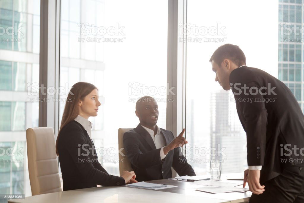 Businessman arguing with multi-ethnic partners stock photo