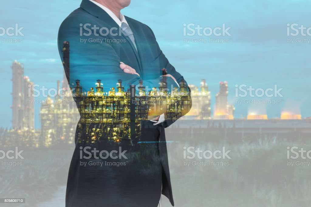 Businessman arms crossed and Electric generating factory industry in night stock photo