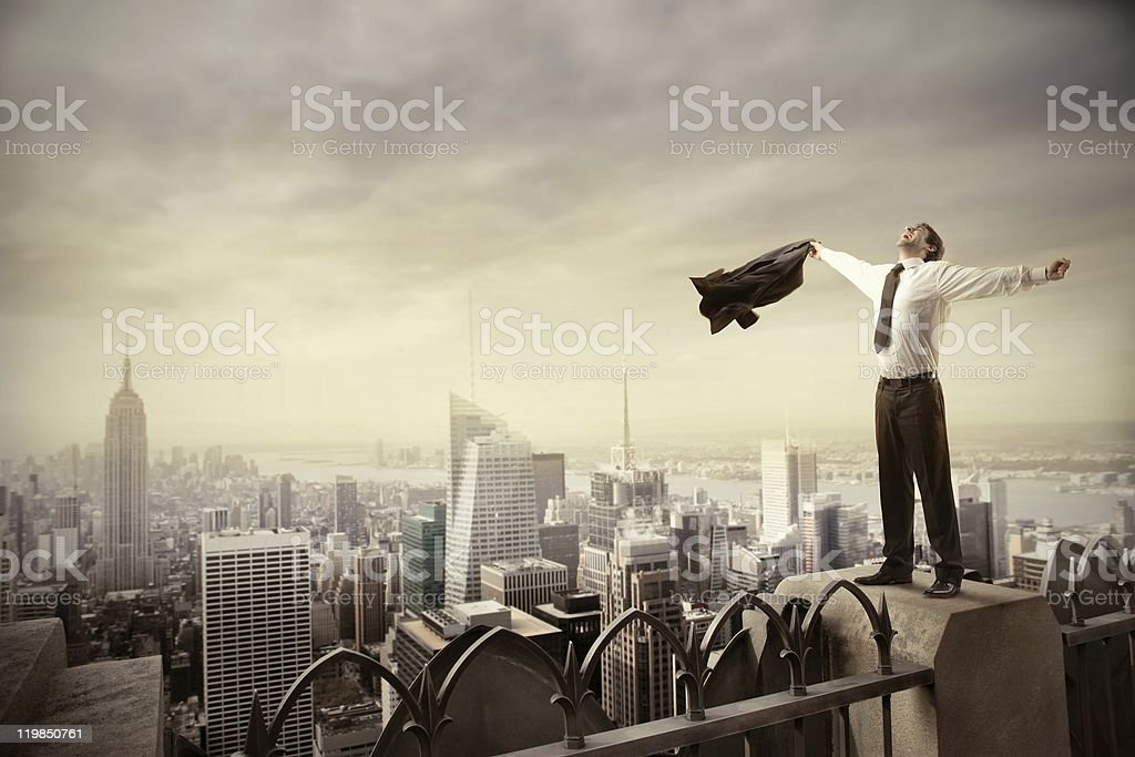 Businessman arms spread on rooftop with skyscraper stock photo