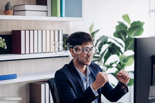 businessman arms up infront of desktop computer get excite about good success new in modern office