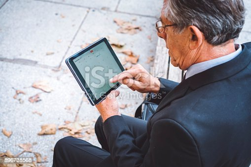 istock Businessman arranging scrolling through his mail on the tablet 896738568