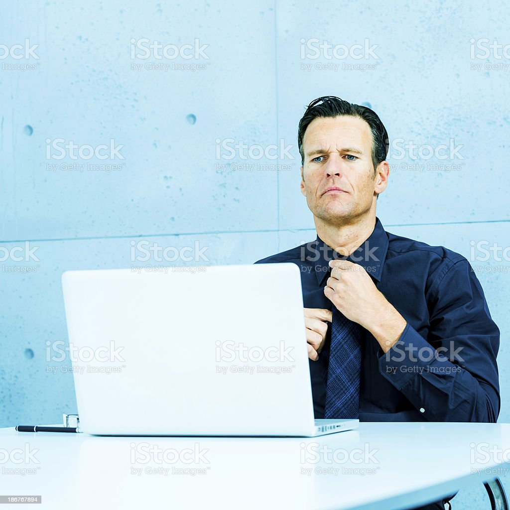Businessman arranging tie for videoconference royalty-free stock photo