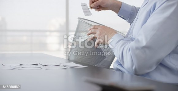 istock Businessman arranging torn paper 647259562