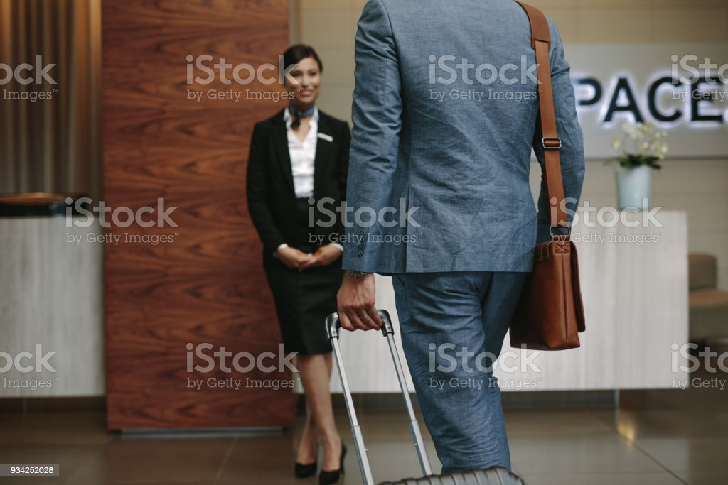 Businessman carrying suitcase and walking towards a receptionist...