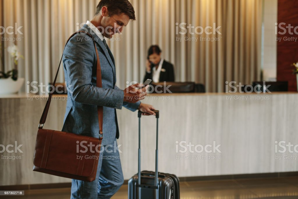 Businessman arriving at hotel lobby stock photo