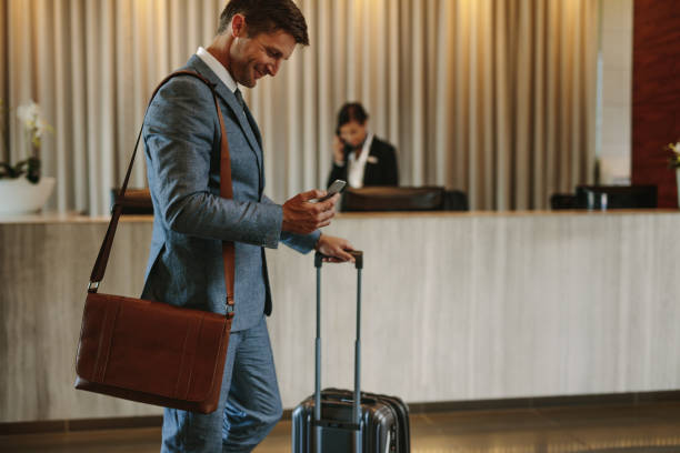businessman arriving at hotel lobby - business travel stock photos and pictures