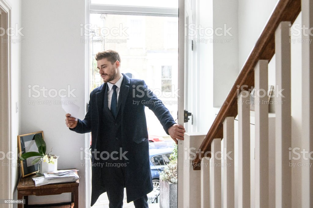 Businessman arriving home and checking post in hallway stock photo