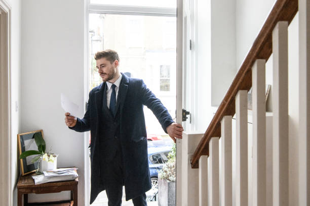 businessman arriving home and checking post in hallway - arrival stock photos and pictures