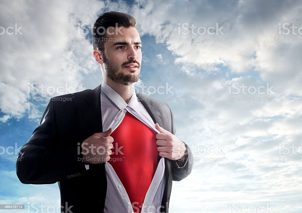 Businessman as superhero over sky background stock photo