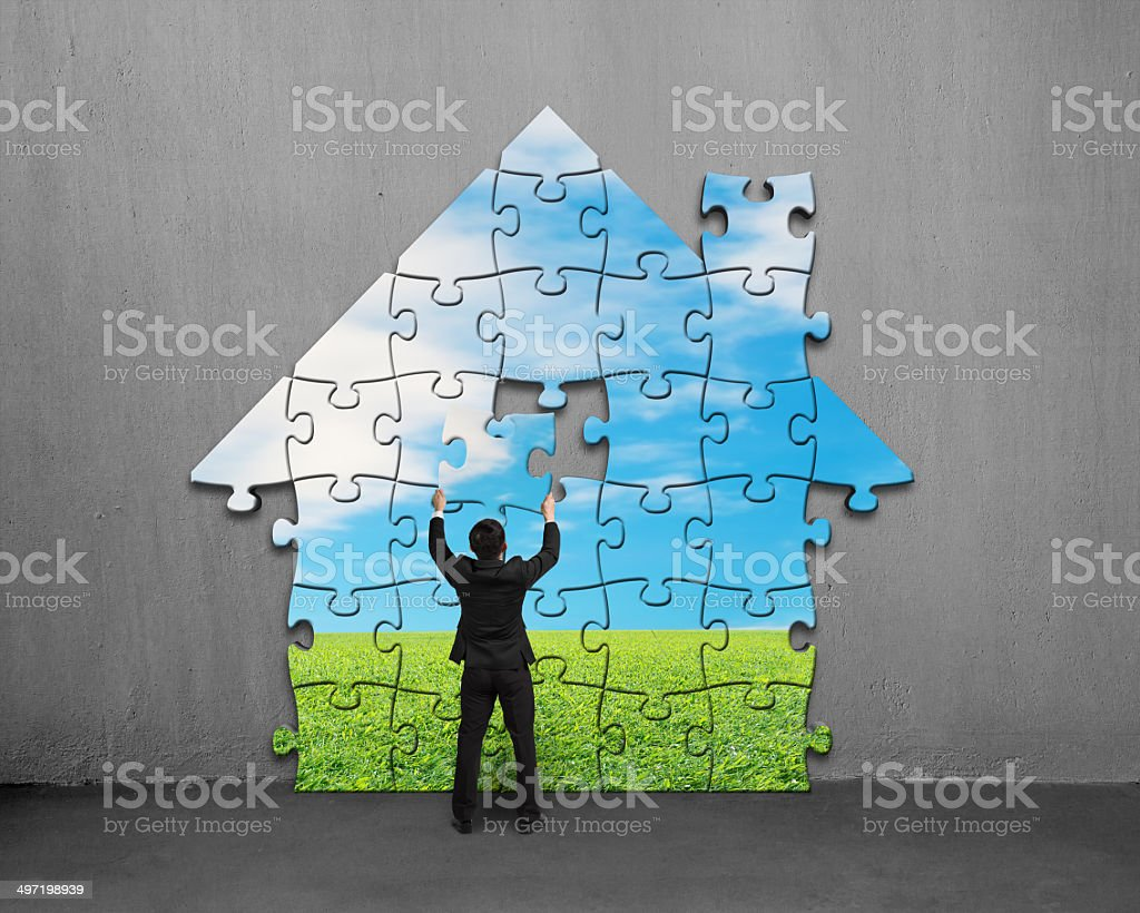 Businessman assembling house shape puzzles with beautiful landsc stock photo