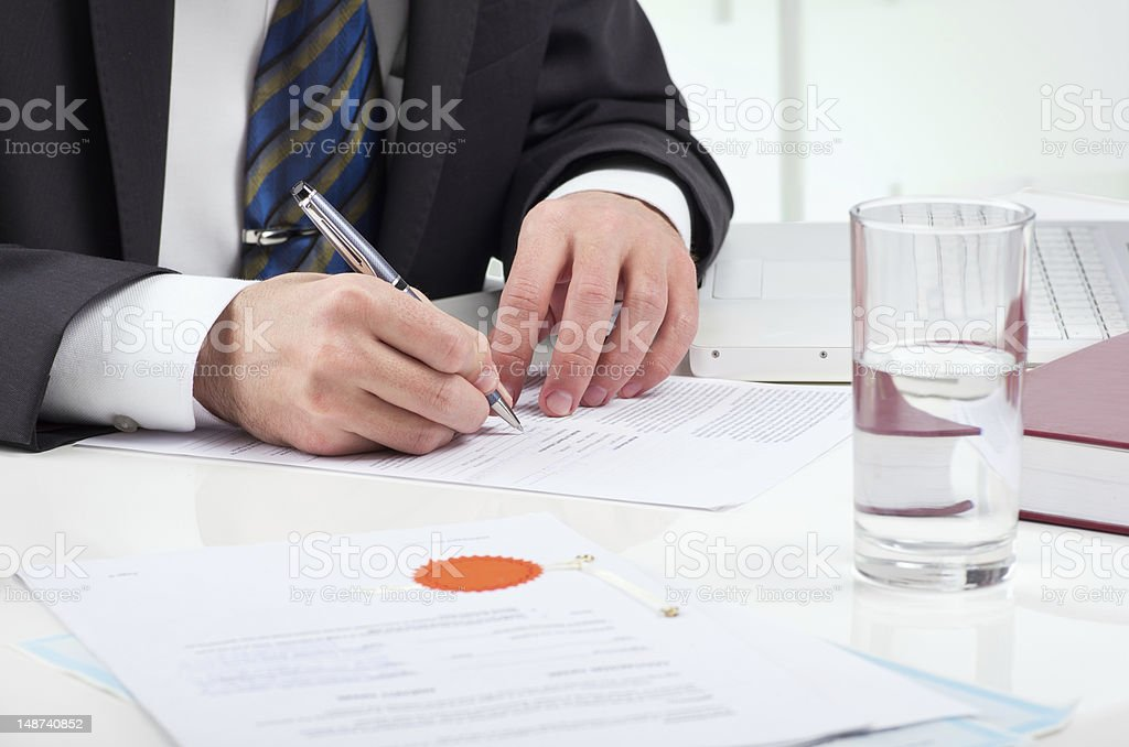 A businessman at a table signing a paper royalty-free stock photo