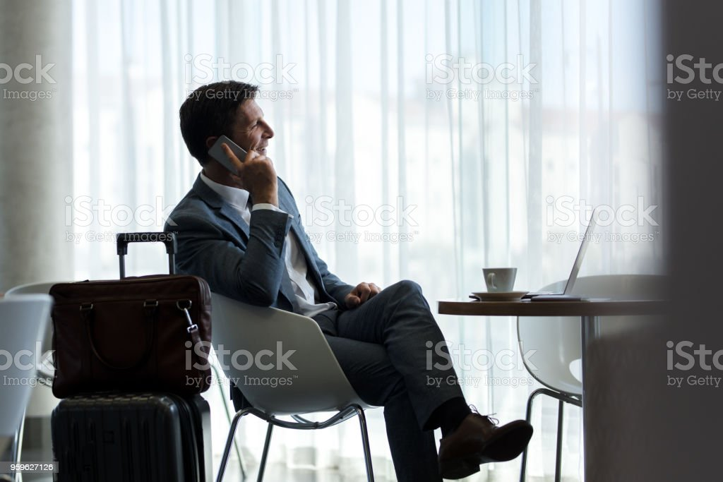 Businessman at airport lounge talking on phone stock photo