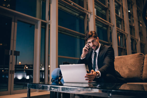 Businessman at airport lounge using laptop and cellphone stock photo
