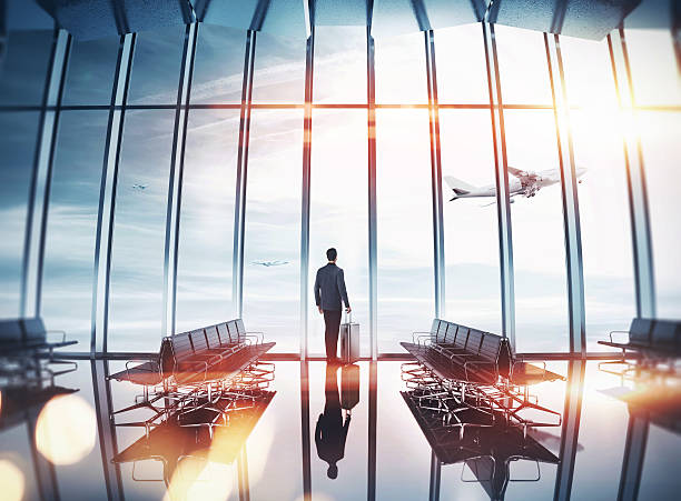 businessman at airport near the window - business travel stock photos and pictures
