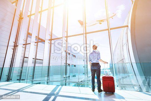 istock Businessman at airport terminal boarding gate looking at airplane flying 689838618