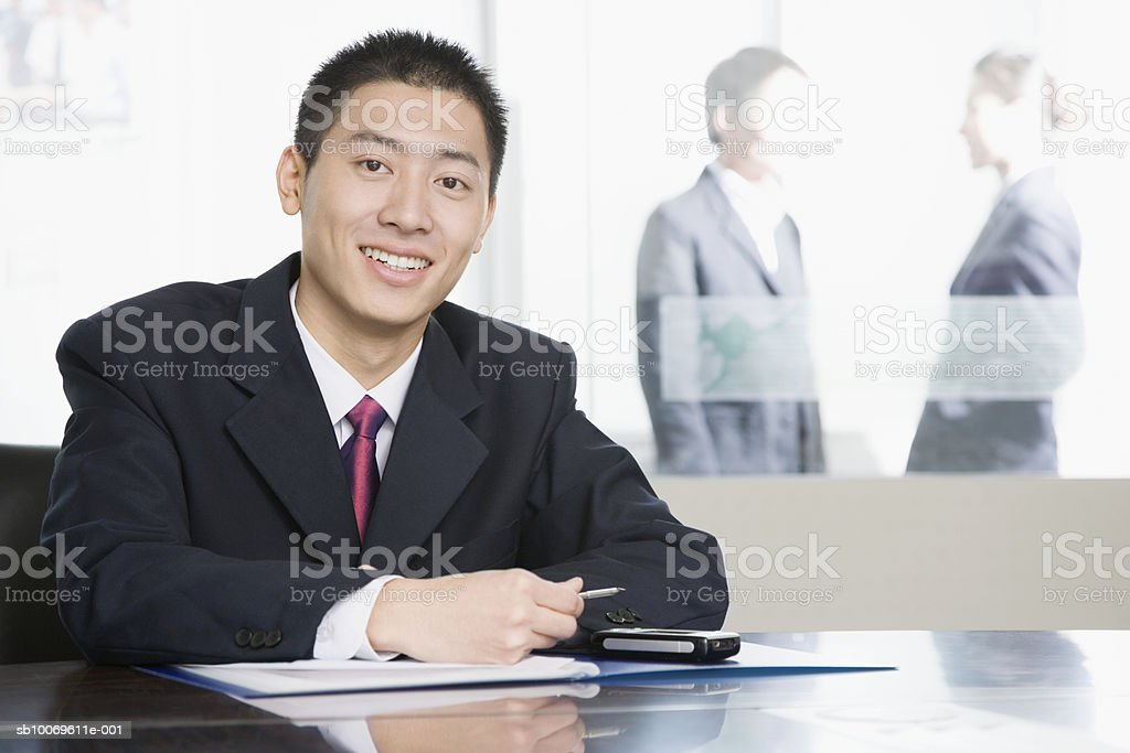 Businessman at conference table, smiling Lizenzfreies stock-foto