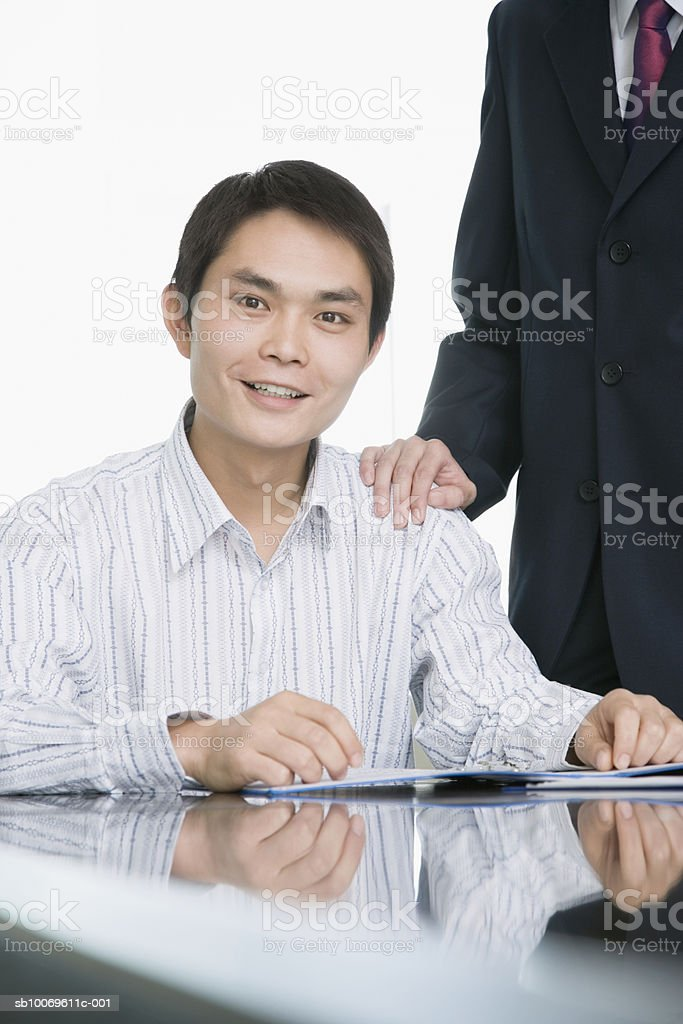 Businessman at conference table, smiling, portrait foto royalty-free