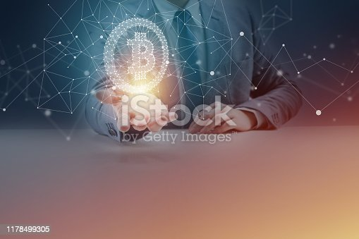 istock Businessman at Desk Holding Bitcoin Symbol and Blockchain Network Graphics 1178499305