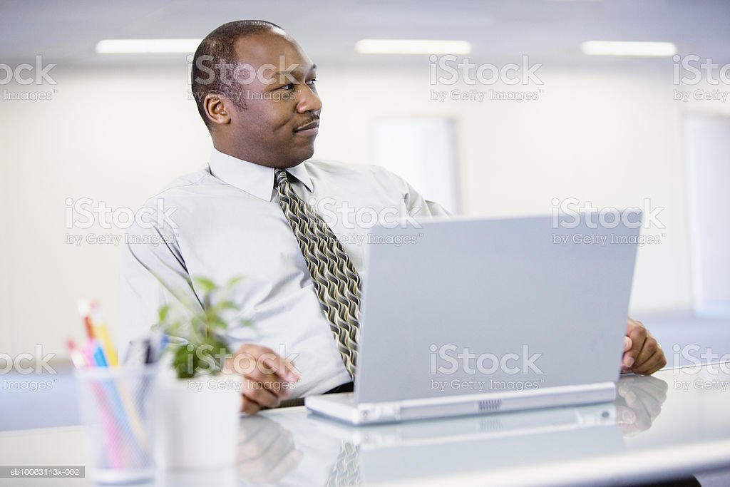Businessman at desk with laptop, smiling royalty-free stock photo