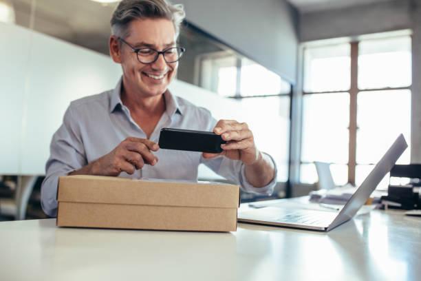 businessman at ecommerce company - owner laptop smartphone foto e immagini stock
