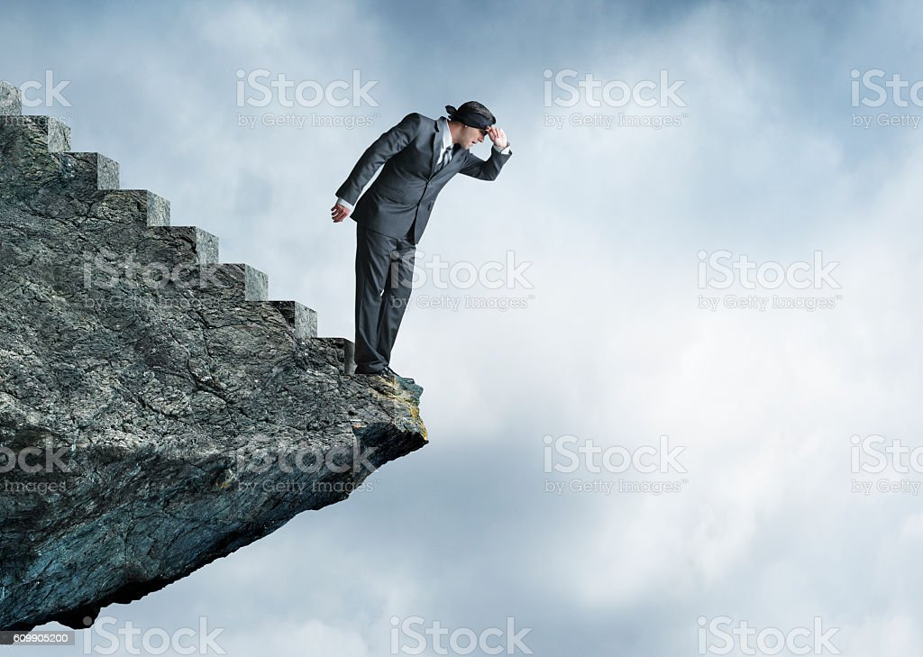 Businessman At End Of Stairs Peeks Out From Blindfold stock photo
