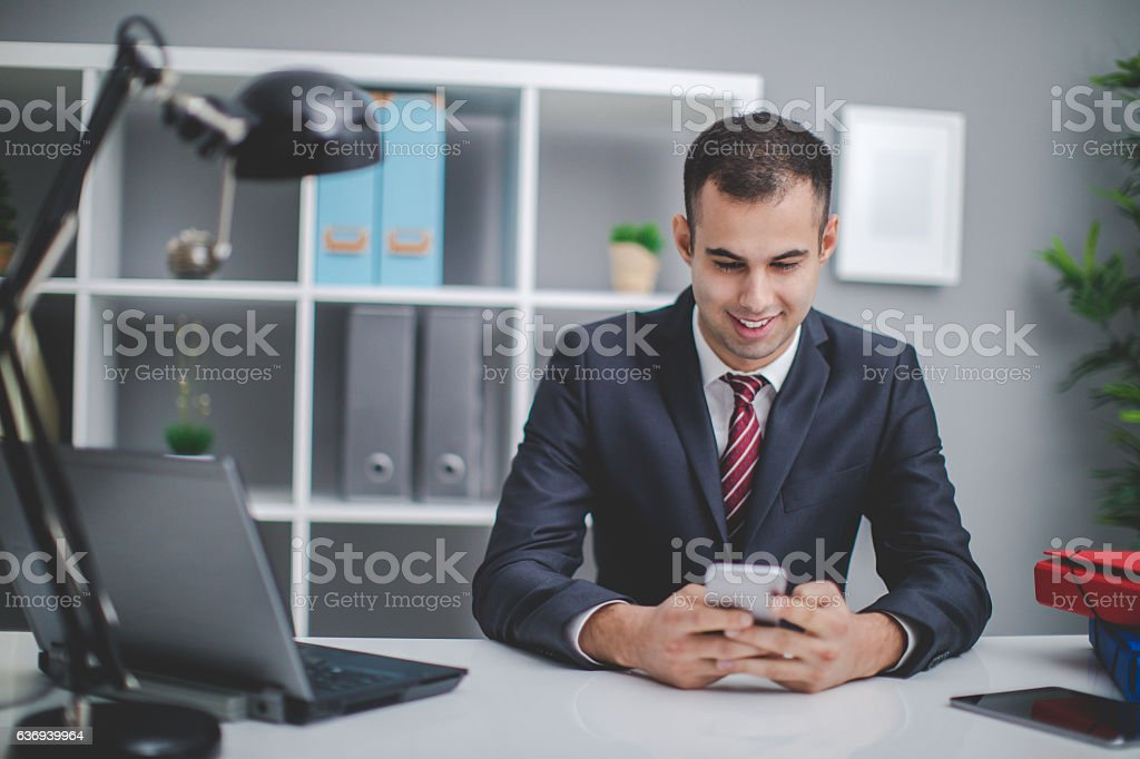 Businessman sitting in the office during work hours, doing work on...