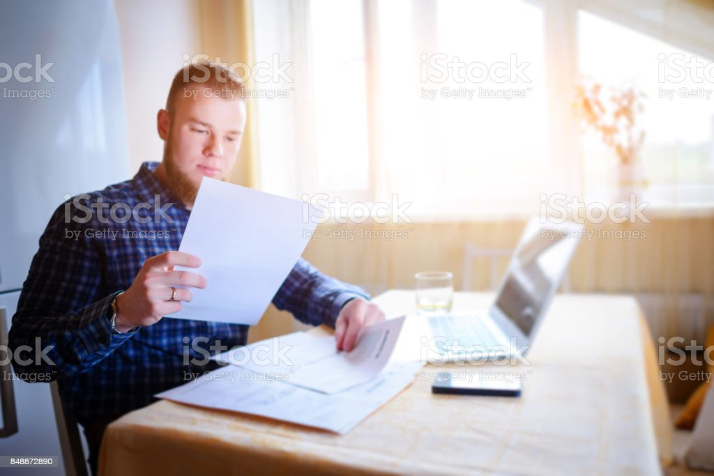 Businessman at home, he is working with a laptop, checking paperwork and bills stock photo